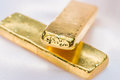 Gold bar gold ingot bars on a soft pink cloth background focus on surface of the macro Royalty Free Stock Images