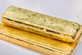 Gold bar gold ingot bars on a soft pink cloth background macro Royalty Free Stock Images