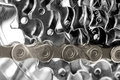 Gold bicycle chain on silver gears Royalty Free Stock Photo