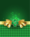 Gold bow with clover golden a brooch in the form of a four leaves on a green plaid background Stock Image