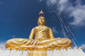 Gold Buddha Image with blue sky and scattering cloud. Royalty Free Stock Photo