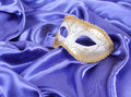 Gold carnival mask on blue silk fabric Royalty Free Stock Photos