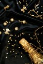 Gold Champagne bottle with confetti stars and party streamers Royalty Free Stock Photo