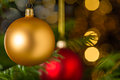 Gold christmas ball hanging on xmas tree bauble sparkling lights background Royalty Free Stock Photos