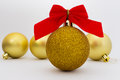 Gold christmas balls with red ribbon on white background shiny Stock Image