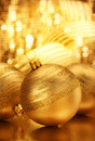 Gold christmas bauble in a golden warm background Stock Photos
