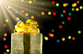 Gold christmas gift box with ribbon and bow on bokeh lights back Royalty Free Stock Photo
