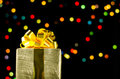 Gold christmas gift box with ribbon and bow on bokeh lights background Royalty Free Stock Photo