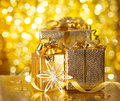 Gold christmas gifts on background of defocused golden lights Royalty Free Stock Photography