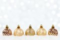 Gold Christmas ornaments in snow with twinkling background Royalty Free Stock Photo