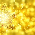 Gold Christmas star on gold background with sparks Royalty Free Stock Photo