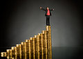 Gold coin businessman stand on top of many rouleau monetary on dark background Royalty Free Stock Photos