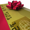 Gold credit card with fancy red ribbon a gift as present on white background in extreme close up Royalty Free Stock Images