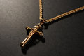Gold cross on a chain on a black background Royalty Free Stock Photo