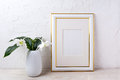 Gold decorated frame mockup with tender white lily in vase Royalty Free Stock Photo