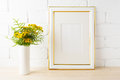 Gold decorated frame mockup yellow flowers near painted brick w