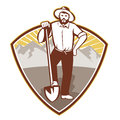 Gold digger miner prospector shield illustration of a with shovel spade done in retro style set inside with mountains in Stock Image