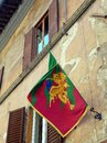 Gold dragon flag siena italy contrade mounted on traditional italian stucco building Stock Photo