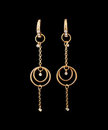 Gold earrings over black background Stock Photo