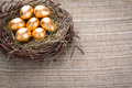 Gold eggs in nest from hay close up Royalty Free Stock Photo