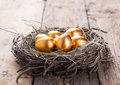 Gold eggs in nest from hay on wood boards Royalty Free Stock Image