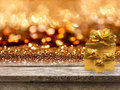 Gold gift boxes and ribbon on wood table, bokeh background Royalty Free Stock Photo
