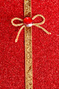 Gold gift ribbon bow on red shiny bacgkround Stock Photo