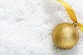 Gold glitter bauble on snow Royalty Free Stock Photo