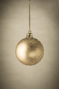 Gold glitter christmas bauble a single sparkling hanging on gilt string with clasp against a parchment background with vignette to Stock Photo