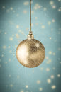 Gold glitter christmas bauble on turqoise with stars photograph of a layered twinkling and sparkling against vignetted turquoise Royalty Free Stock Photo
