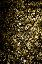 Gold glitter texture isolated on black square. Amber particles c