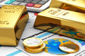Gold ingots and coins on financial reports Royalty Free Stock Photos
