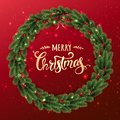 Gold Merry Christmas Typographical on red background with Christmas wreath of tree branches, berries, lights, bokeh.