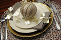 Gold metallic theme Christmas  formal dinner table place setting. Close up. Royalty Free Stock Photo