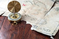 Gold nautical compass on old retro pirate map with red mark cross. Fake treasure map on wooden table Royalty Free Stock Photo