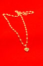 Gold necklace with heart on red background Royalty Free Stock Images