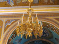 Gold ornated luxurious luster in interior of church Stock Photos