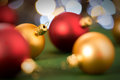 Gold and red christmas baubles on green lights background Stock Images