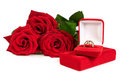 Gold ring in a red gift box with a bouquet of roses isolated on white Stock Photos
