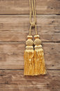 Gold rope with curtain tassel against wooden wall Royalty Free Stock Photography