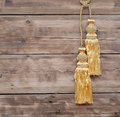 Gold rope with curtain tassel against wooden wall Royalty Free Stock Photo