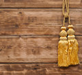 Gold rope with tassel against wooden wall Stock Images