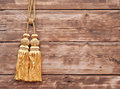 Gold rope with tassel against wooden wall Royalty Free Stock Photo