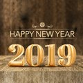 Gold shiny Happy New year 2019 3d rendering at wooden block table and blur wood wall,Holiday greeting card for social media. Royalty Free Stock Photo