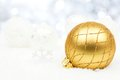 Gold and silver Christmas ornaments in snow with twinkling background Royalty Free Stock Photo