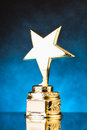 Gold star against blue particles background trophy Royalty Free Stock Photography