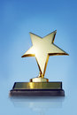 Gold star award on the stand against blue background Stock Images