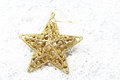 The gold star on snow for decoration christmas Royalty Free Stock Photo