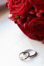 Gold wedding rings and bridal bouquet close up Royalty Free Stock Image