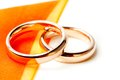 Gold wedding rings near orange ribbon detail of Royalty Free Stock Photography